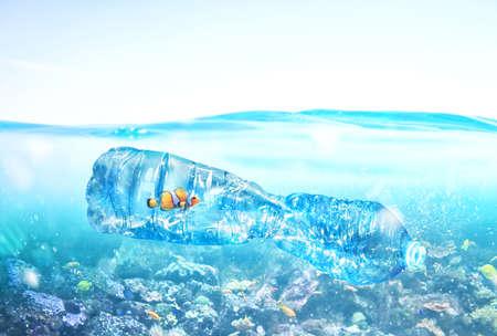 Photo pour Fish trapped inside a bottle. Problem of plastic pollution under the sea concept. - image libre de droit