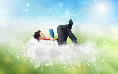 Photo for Businessman reads a book over a cloud made of letters. - Royalty Free Image
