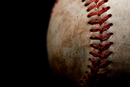 an abstract macro of a used baseball with focus on a set of stitches shot over black mural