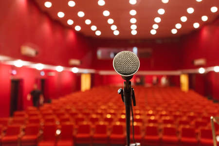 Photo for microphone on a background of red hall with seating for spectators. chairs for the audience - Royalty Free Image
