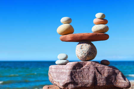 Photo for Symbolic scales of stones against the background of the sea and blue sky. Concept of harmony and balance. Pros and cons concept - Royalty Free Image