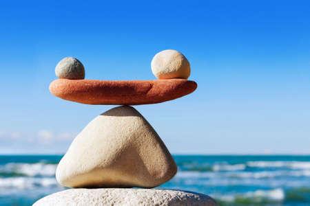 Foto de Concept of harmony and balance. Balance stones against the sea. Rock zen in the form of scales - Imagen libre de derechos