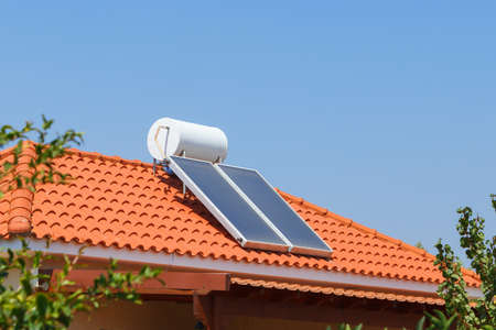 Photo pour Solar water heating panel and water collector on a house roof - image libre de droit