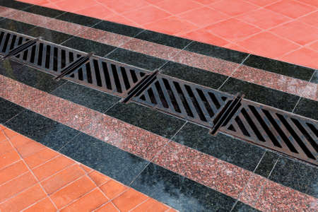 Photo pour Pedestrian covering, lined with granite tiles with metal drainage grate. Sidewalk drainage system - image libre de droit