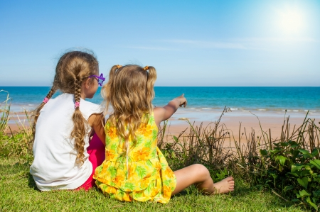 Photo pour Two girls sitting on the beach and watching the sea - image libre de droit