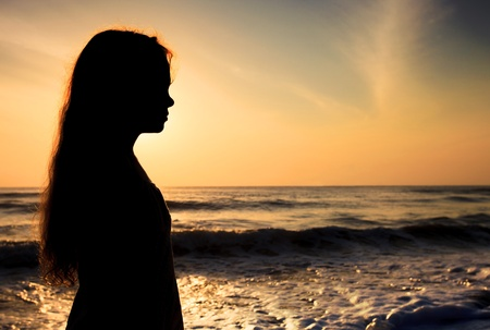 Silhouette of a sad child on the beach