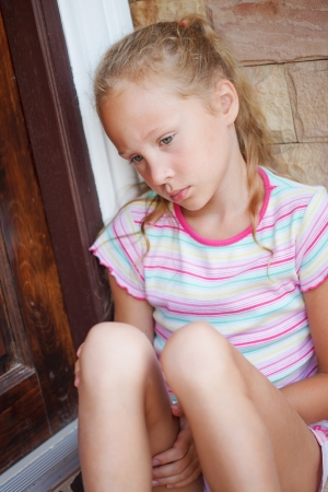 Photo for sad little girl sitting near a door on the background of an brick wall - Royalty Free Image
