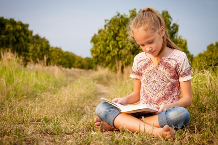 Photo for little girl sitting and reading a book on nature - Royalty Free Image