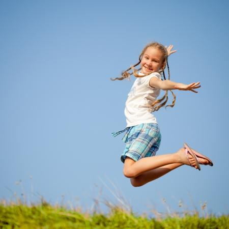 little girl jumping over the grass