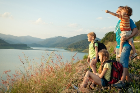Photo pour Happy family watching the sunset on the lake - image libre de droit