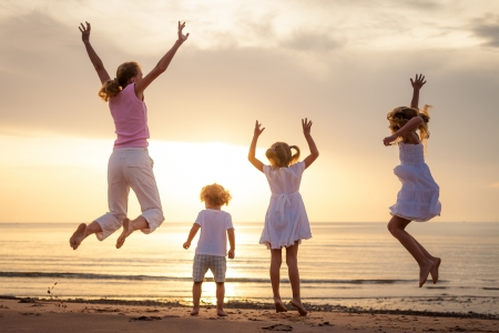 Foto de Happy beautiful family dancing on the  beach on the  dawn time  - Imagen libre de derechos