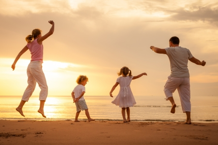 Foto de Happy beautiful family dancing on the  beach on the  dawn time  - Imagen libre de derechos