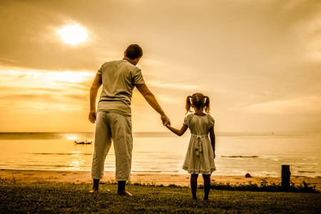 Foto de father and daughter standing at the beach in the dawn time - Imagen libre de derechos