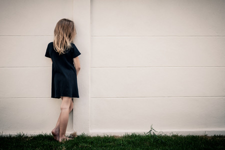 Foto de Portrait of sad little girl standing near wall in the day time - Imagen libre de derechos