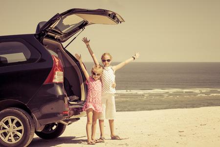 Photo pour two sisters standing near a car on the beach - image libre de droit