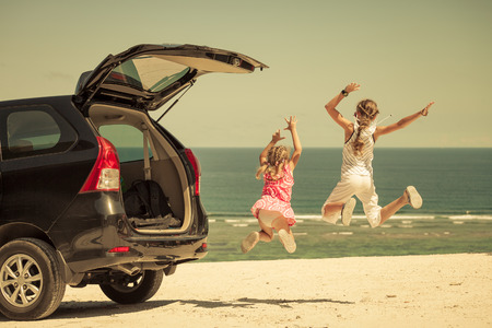 Photo pour two sisters standing near a car on the beach - image libre de droit