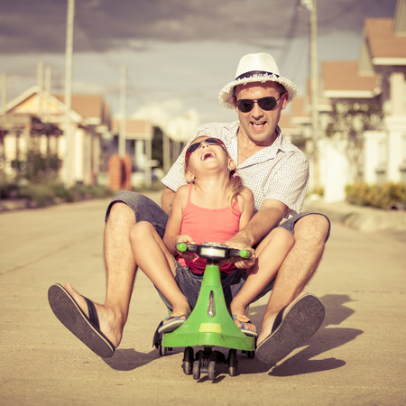 Foto de father and little daughter playing near a house at the day time - Imagen libre de derechos