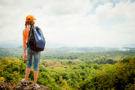 Photo pour teenager with a backpack standing on a mountain top - image libre de droit