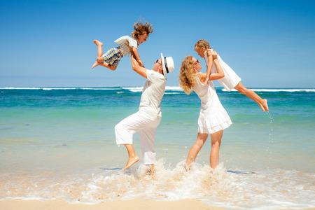 Foto de Happy family playing on the beach at the day time - Imagen libre de derechos