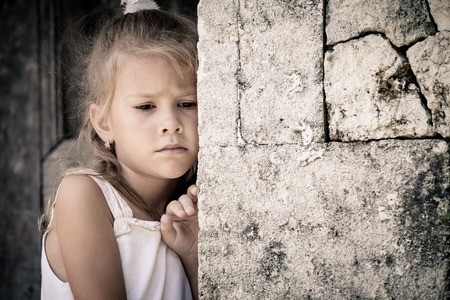 Foto de Portrait of sad little girl standing near stone wall at the day time - Imagen libre de derechos