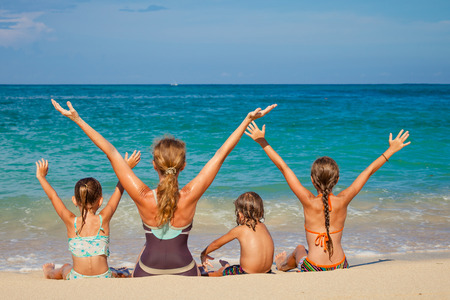Photo pour Happy family sitting on the beach at the day time - image libre de droit
