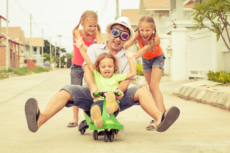 Photo for father and children playing near a house at the day time - Royalty Free Image