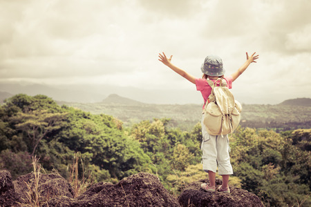 Photo pour little girl with a backpack standing on a mountain top at the day time - image libre de droit