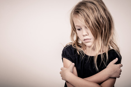 Foto de Portrait of sad blond little girl standing near wall - Imagen libre de derechos