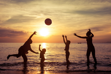 Photo pour Silhouette of happy family who playing with the ball on the beach at the sunset time. Concept of friendly family. - image libre de droit