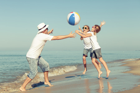 Foto de Father and daughters playing on the beach at the day time. Concept of friendly family. - Imagen libre de derechos