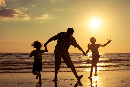 Photo pour Father and children playing on the beach at the sunset time. Concept of friendly family. - image libre de droit