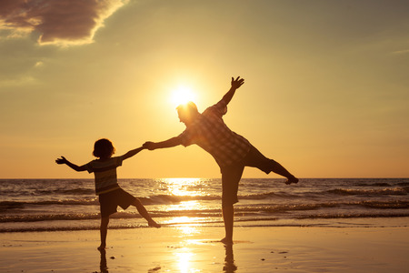 Foto per Father and son playing on the beach at the sunset time. Concept of friendly family. - Immagine Royalty Free