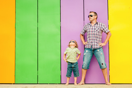 Photo for Father and son playing near the house at the day time. They standing near are the colorful wall. Concept of friendly family. - Royalty Free Image