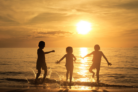 Photo for Happy children playing on the beach at the sunset time - Royalty Free Image