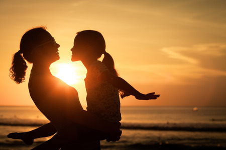 Photo pour Mother and daughter playing on the beach at the sunset time. Concept of friendly family. - image libre de droit