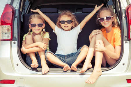 Photo pour Happy brother and his two sisters are sitting in the car at the day time - image libre de droit