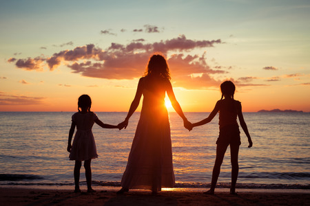 Photo for Mother and daughters standing on the beach at the sunset time. Concept of friendly family. - Royalty Free Image