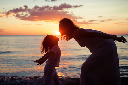 Photo pour Mother and son playing on the beach at the sunset time. Concept of friendly family. - image libre de droit