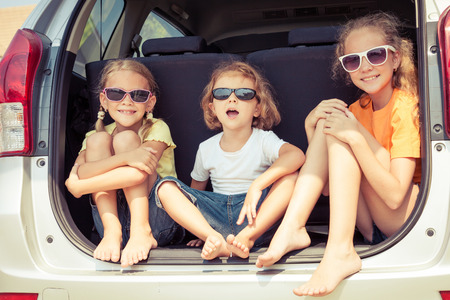 Photo for Happy brother and his two sisters are sitting in the car at the day time - Royalty Free Image