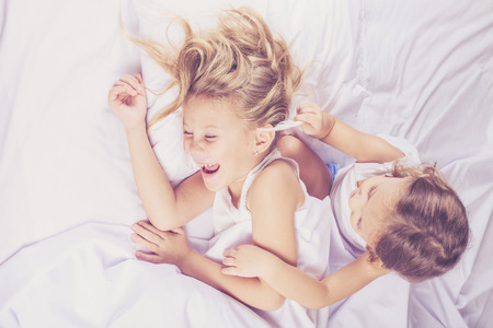 Photo pour Lovely brother and sister lying in bed at home. Concept of Brother And Sister Together Forever - image libre de droit