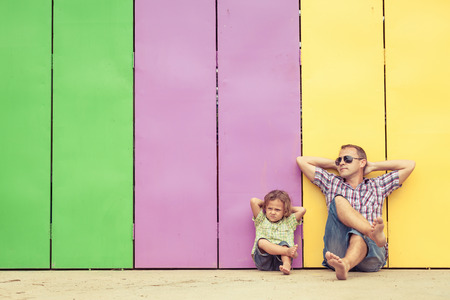 Foto de Father and son playing near the house at the day time. They sitting near are the colorful wall. Concept of friendly family. - Imagen libre de derechos