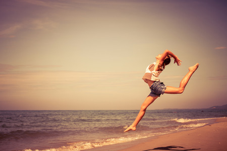 Photo pour Teen  girl  jumping on the beach at the day time - image libre de droit