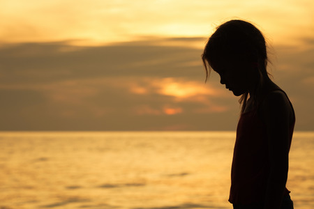Foto de Portrait of sad blond little girl standing on the beach at sunset time. - Imagen libre de derechos