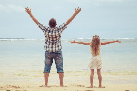 Foto de Father and daughter playing on the beach at the day time. Concept of friendly family. - Imagen libre de derechos