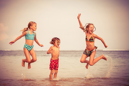 Photo for Three happy children  playing on the beach at the day time - Royalty Free Image