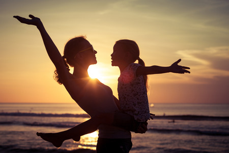 Foto de Mother and daughter playing on the beach at the sunset time. Concept of friendly family. - Imagen libre de derechos