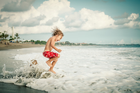Foto de Portrait of little boy jumping on the beach at the day time - Imagen libre de derechos