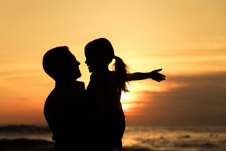 Photo for Father and daughter  playing on the beach at the sunset time. Concept of friendly family. - Royalty Free Image