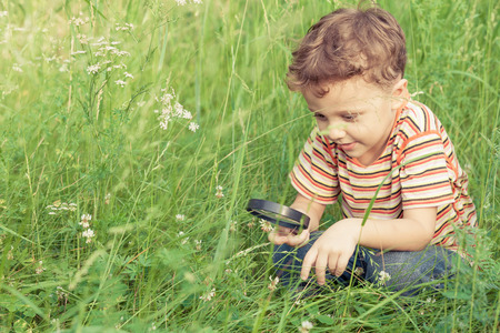 Photo for Happy little boy exploring nature with magnifying glass at the day time - Royalty Free Image