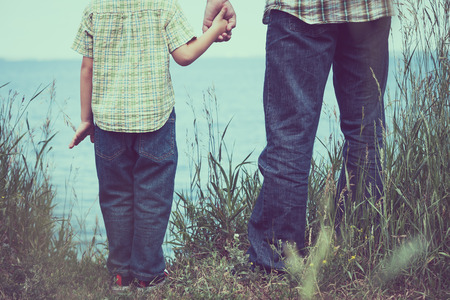 Photo for Father and son standing at the park near lake at the day time. Concept of friendly family. - Royalty Free Image